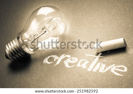 Handwriting of Creative word with glowing light bulb - stock photo