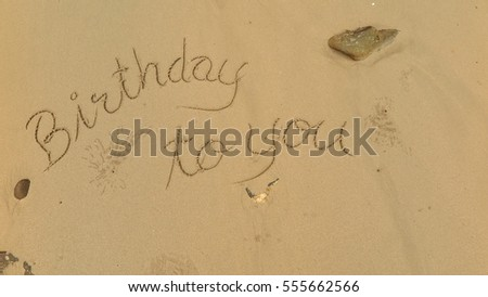 "Handwriting words ""Birthday to you"" on sand of beach"