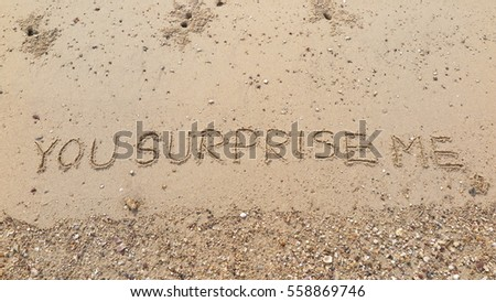 "Handwriting words ""YOU SURPRISE ME"" on sand of beach"