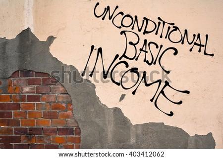 Handwritten graffiti Unconditional Basic Income sprayed on the wall, anarchist aesthetics - stock photo