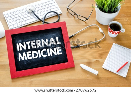 Handwritten internal-medicine on blackboard. Handwritten internal-medicine with chalk on blackboard,stethoscope, keyboard,notebook,glasses,cup of coffee and green plant on wooden background - stock photo