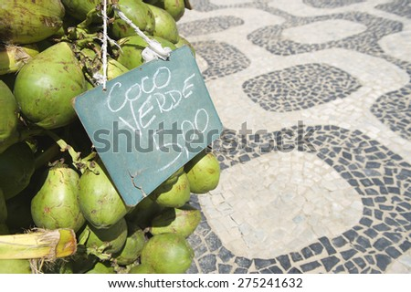 Handwritten sign advertising the price in Brazilian reals resting on bunch of fresh green Brazilian coco verde coconuts hanging at Ipanema Beach boardwalk in Rio de Janeiro Brazil - stock photo