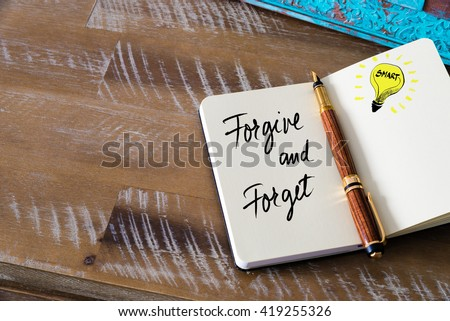 Handwritten text Forgive and Forget with fountain pen on notebook. Concept image with copy space available. - stock photo