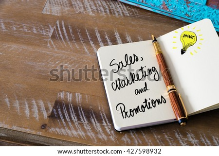 Handwritten text Sales, Marketing and Promotions with fountain pen on notebook. Concept image with copy space available. - stock photo