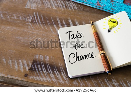 Handwritten text Take The Chance with fountain pen on notebook. Concept image with copy space available. - stock photo