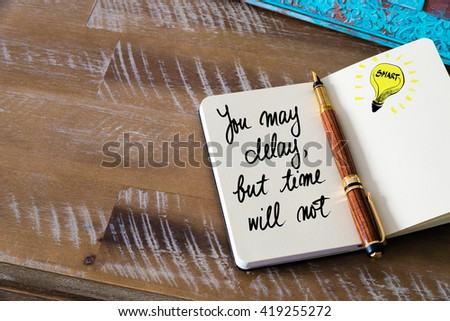 Handwritten text You May delay, But Time Will Not with fountain pen on notebook. Concept image with copy space available. - stock photo