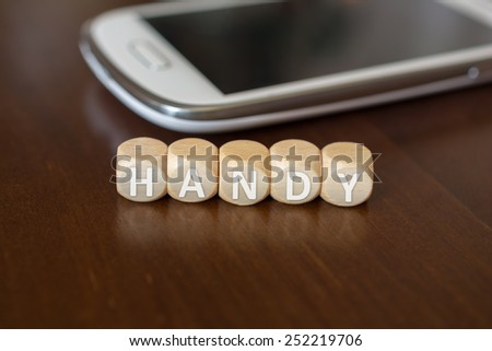 HANDY Blocks Besides A White Smartphone On A Wooden Table