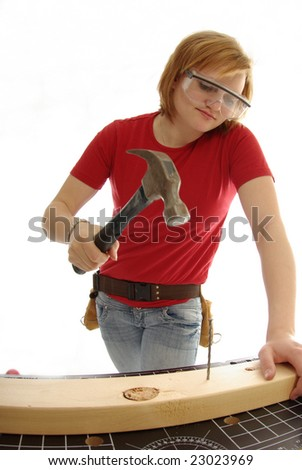 Handy girl gets ready to hammer a nail into a piece of wood. - stock photo