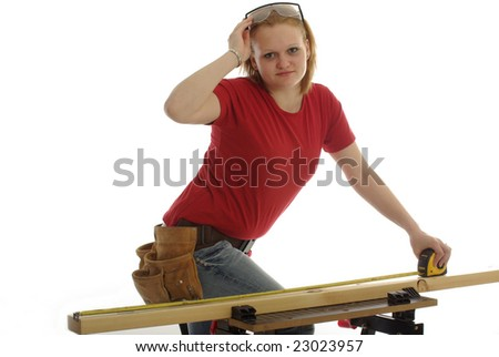 Handy girl measures a 2x4 piece of wood - stock photo