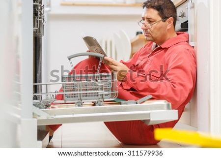 Handy man figuring out a way to fix the dishwasher in the kitchen.