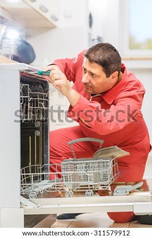 Handy man taking apart a broken dishwasher to fix it in the kitchen. - stock photo