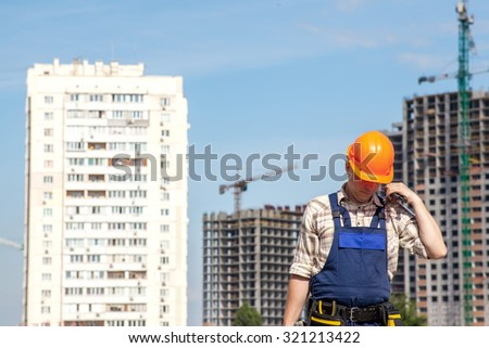 Handyman builder on the background of a construction site. Orange helmet on the head for safety.