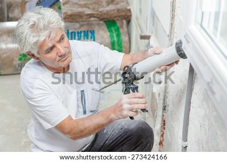 Handyman caulking a window frame - stock photo