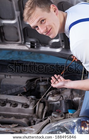 Handyman during checking engine oil level, vertical - stock photo