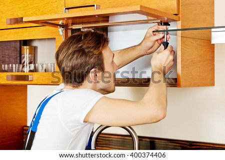 Handyman fixing kitchen's cabinet with screwdriver - stock photo