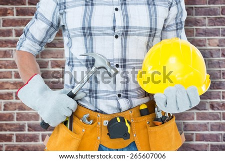 Handyman holding hammer and hard hat against red brick wall