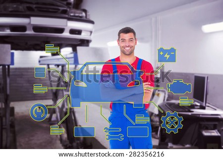 Handyman in overalls standing arms crossed over white backgound against auto repair shop - stock photo