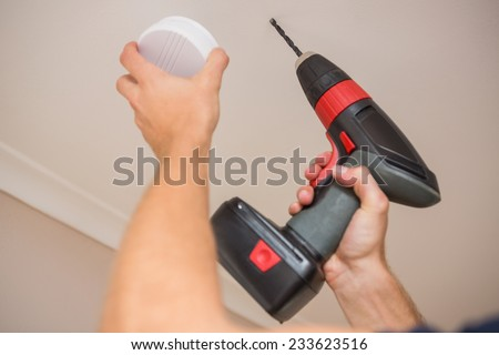 Handyman installing smoke detector with power tool on the ceiling - stock photo