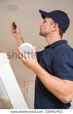 Handyman installing smoke detector with screwdriver on the ceiling - stock photo