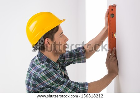 Handyman measuring wall. Confident craftsperson in hardhat measuring the wall level
