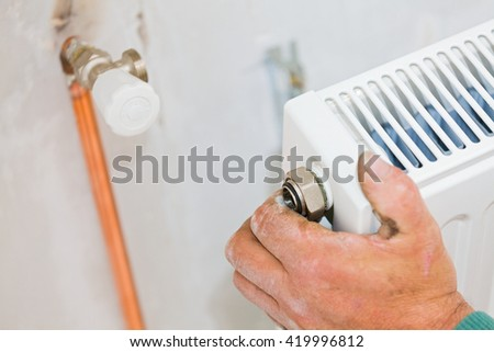 Handyman mounting radiator to fix home heating system.