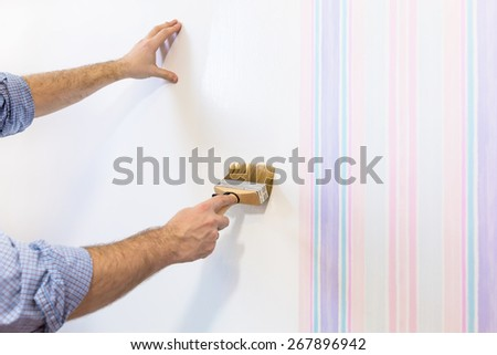 Handyman painting wall with background glue for a wallpaper - stock photo