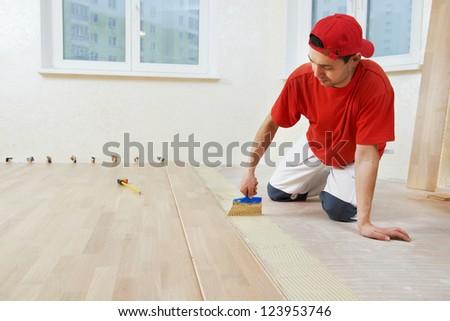 Handyman parquet carpenter worker adding glue on base during wood flooring - stock photo