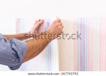 Handyman putting up wallpaper on the white walls - stock photo