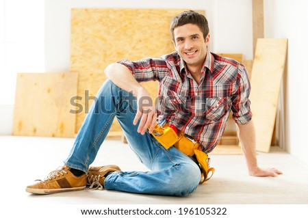 Handyman relaxing. Handsome young handyman in talking on the mobile phone and smiling while sitting on the floor  - stock photo