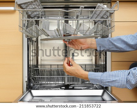 handyman repairing a dishwasher - stock photo