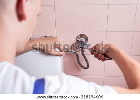Handyman repairing a pipe with a wrench - stock photo