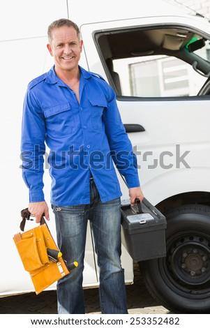 Handyman smiling at camera holding toolbox by his van - stock photo