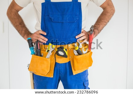 Handyman standing in tool belt in a new house - stock photo