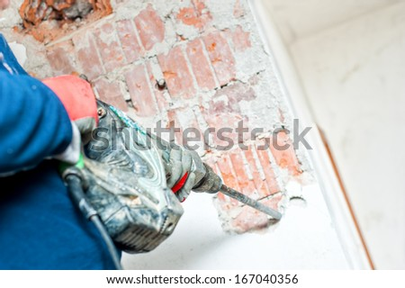 handyman using a jackhammer to destroy concrete interior walls - stock photo