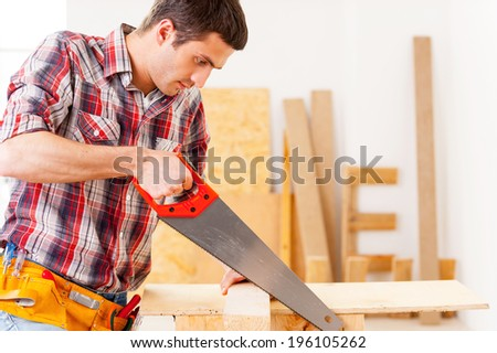 Handyman using saw. Confident young handyman using saw in workshop - stock photo