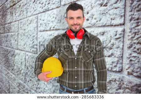 Handyman with earmuffs holding helmet against grey brick wall - stock photo