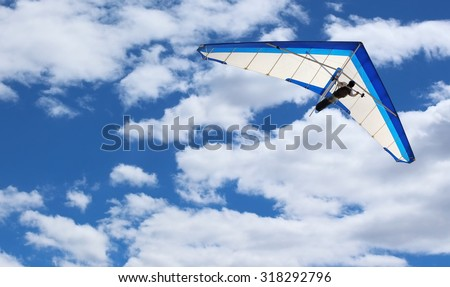 Hang Glider flying in Kitty Hawk North Carolina on a clear, bright, blue sunny day with clouds in the sky - stock photo