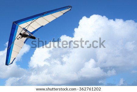 Hang Glider flying through the sky white puffy clouds - stock photo