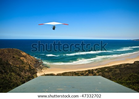 Hang Glider Launches From Hill Above Byron Bay Beach on a Sunny Day