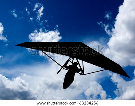 Hang glider silhouette superimposed against a cloudscape