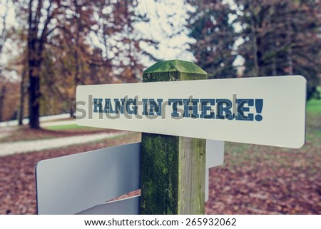 Hang In There motivational message on a rustic signboard on a wooden pole in an autumn park, angled perspective with a vintage style filter effect. - stock photo