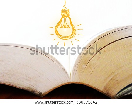 hang out idea light bulb with big blur book , business idea concept - stock photo