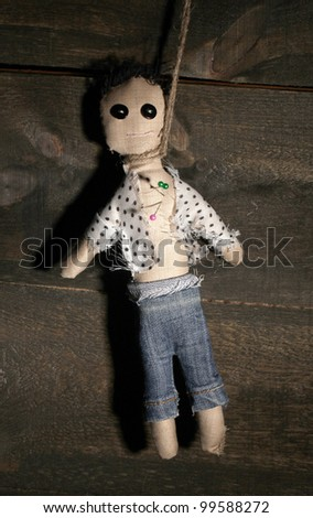Hanged doll voodoo boy on wooden background - stock photo