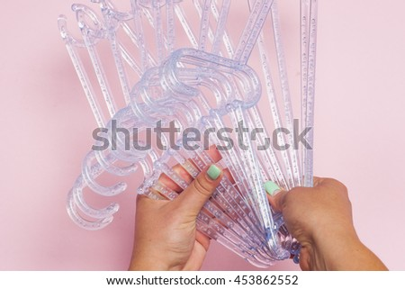 Hangers isolated on the pink background. Choosing clothes hangers. Female hands closeup. - stock photo
