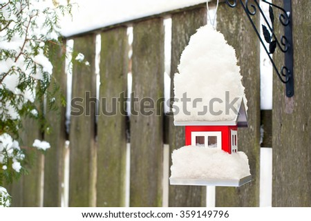 Hanging bird red metal feeder covered by snow in winter. Outdoors horizontal closeup image. - stock photo