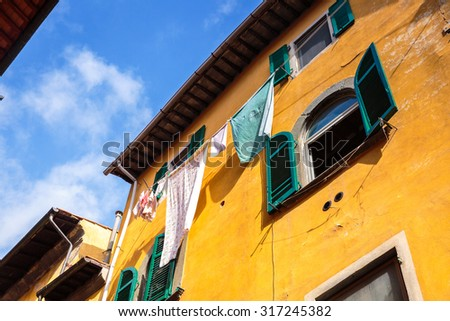 Hanging clothes on a beautiful building in Pisa, Italy - stock photo