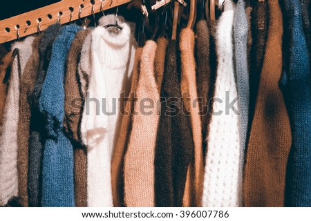 Hanging colorful  knitted colorful clothes - sweaters, dresses, cardigans etc. Toned photo. - stock photo