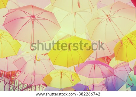Hanging colorful umbrellas  backgroundon the street and blue sky.Colourful umbrellas urban street decoration. Hanging Multicoloured umbrellas. vintage color in Holiday tone,selective focus - stock photo