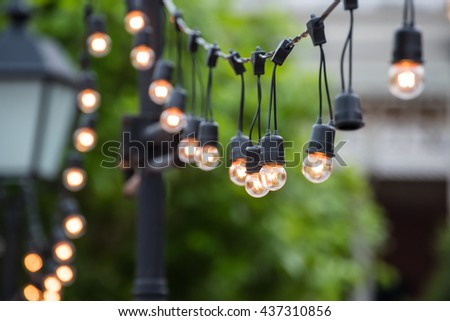 Hanging decorative christmas lights for a ceremony - stock photo