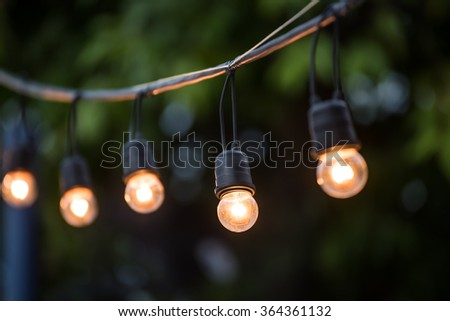 Hanging decorative christmas lights for a wedding ceremony - stock photo